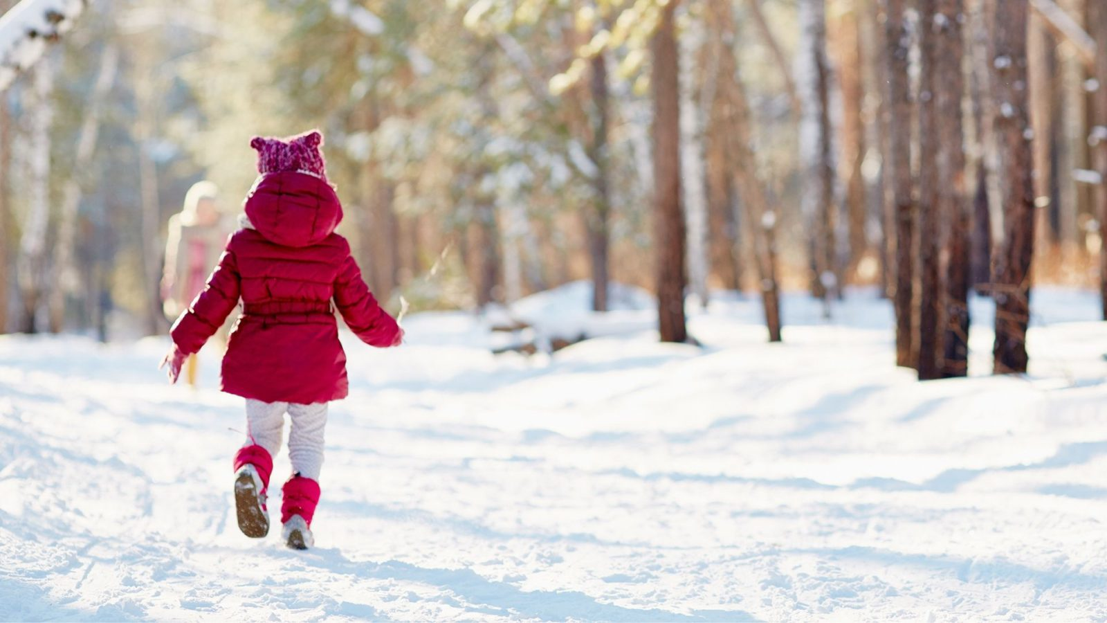 A child in a red jacket, a square knitted pink hat, white leggings, and red boots walks cheerfully down a snowy path. Trees surround either side of the path.