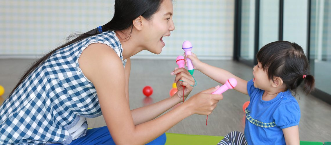 Mother and Cute asian baby girl playing plastic microphone at the Kid room