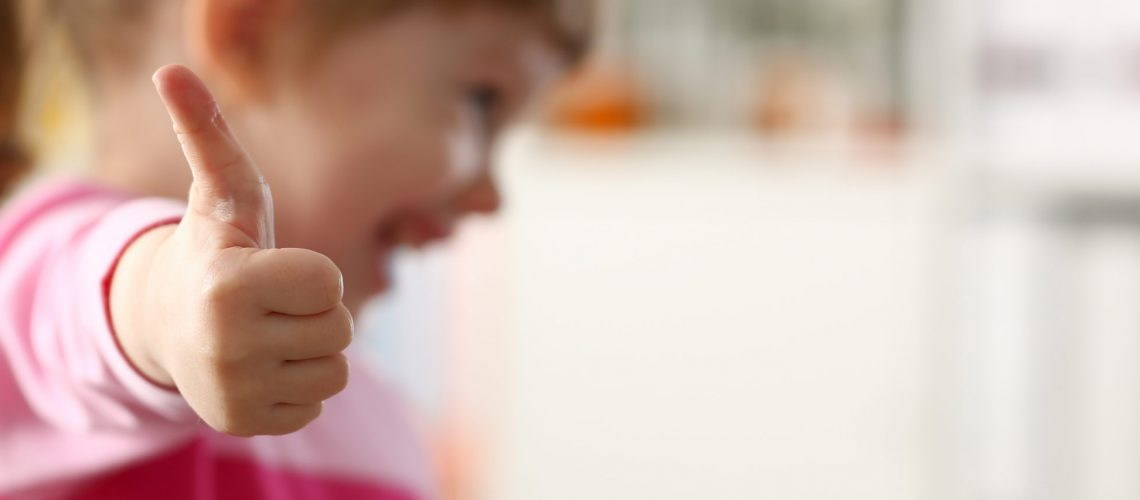 Little girl show approve or OK sign with her arm closeup